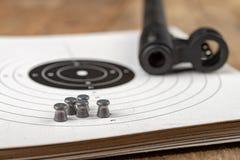 Ett pneumatiskt vapen på en trätabell på en skjutbana Skyttetillbehören behövde för att skjuta sportar arkivfoto