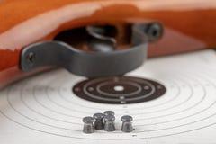 Ett pneumatiskt vapen på en trätabell på en skjutbana Skyttetillbehören behövde för att skjuta sportar arkivfoton