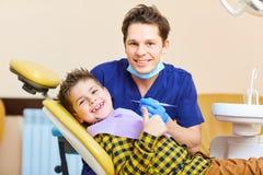 Ett pojkebarn och en tandläkareman lyftte deras tummar Arkivfoton
