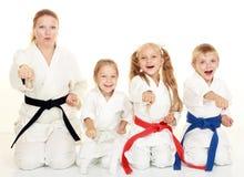 Ett pojkesammanträde med hans syster och mamman med hennes dotter i en ritual poserar karate och slår hans näve Arkivfoto