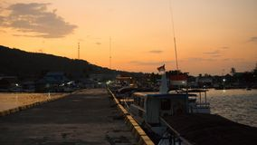Ett portdäck som är litet på den avlägsna ön på soluppgång med svart skugga och orange himmel arkivbilder