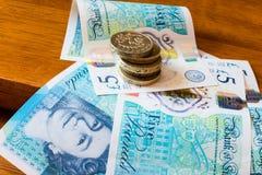 Ett pund mynt och det nya 5 pundet noterar A Arkivfoto