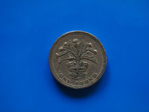Ett pundGBP mynt, Förenade kungariket UK över blått Fotografering för Bildbyråer