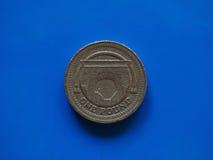 Ett pundGBP mynt, Förenade kungariket UK över blått Arkivfoton