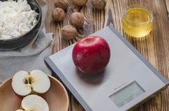 Ett rött äpple ligger på en metallskala på en trätabell, bredvid det är en platta med keso, en platta med ett klippt äpple, muttr royaltyfria foton