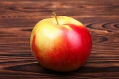Ett rött äpple på en träbakgrund Ett färgrikt och sött äpple Ett healthful och näringsrikt mellanmål En enkel organisk ingrediens fotografering för bildbyråer