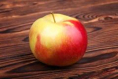 Ett rött äpple på en träbakgrund Ett färgrikt och sött äpple Ett healthful och näringsrikt mellanmål En enkel organisk ingrediens arkivfoton