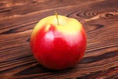 Ett rött äpple på en träbakgrund Ett färgrikt och sött äpple Ett healthful och näringsrikt mellanmål En enkel organisk ingrediens arkivfoto