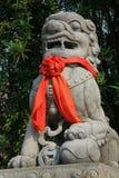 Ett rött band knöts runt om statyn av ett lejon som installerades i borggården av en buddistisk tempel i Hoi An (Vietnam) Arkivfoton