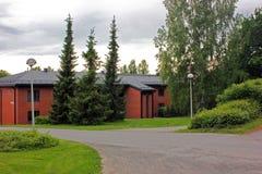Ett rött bygdhus som omges av träd fotografering för bildbyråer
