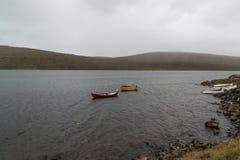 Ett rött fartyg och två gula fartyg i en sjö på Faroe Island Fotografering för Bildbyråer