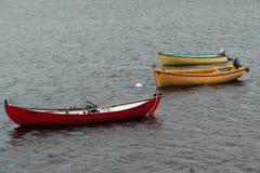 Ett rött fartyg och två gula fartyg i en sjö på Faroe Island Arkivfoton