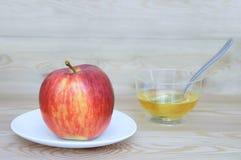Ett rött och gult äpple på en vit platta och honung i en giffel med arkivfoto
