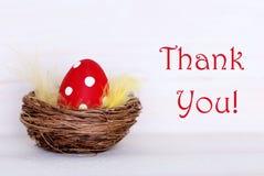 Ett rött påskägg i rede med tackar dig Royaltyfri Foto