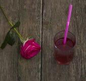 Ett rött ros och exponeringsglas av fruktsaft, på en gammal tabell Royaltyfria Bilder