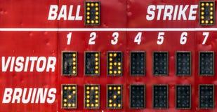 Ett rött ställningbräde på en softballlek Arkivbild