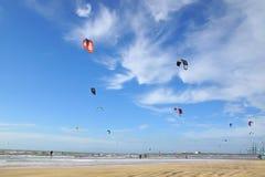 Ett raddafolk som kiteboarding på stranden. Arkivbilder