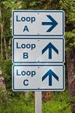 Ett riktningstecken som indikerar olika öglor på en tältplats Royaltyfri Fotografi