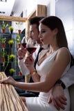 Ett romantiskt par med ett exponeringsglas av vin i matsalen Arkivfoton