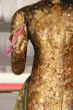Ett rosa band hakas till handen av en staty av Buddha (Thailand) arkivfoto