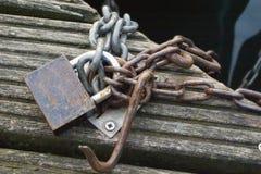 Ett rostigt stort lås med metalliska massiva kedjor på ett träpäron Arkivfoto