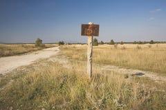 ett rostigt undertecknar in ett ensamt fält royaltyfri fotografi