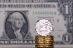 Ett rubelmynt mot en bakgrund av 1 en dollarsedel arkivfoto
