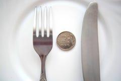Ett rubelmynt på en vit platta royaltyfri foto