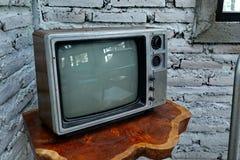 Ett rum med en gammal järnstol och television arkivfoto