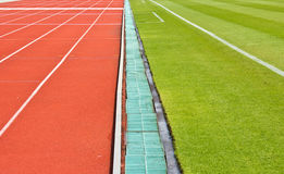 Ett running spår och gräs. Arkivfoto