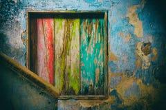 Ett ruttet wood inre fönster som målas i gräsplan, gult och rött Arkivfoto