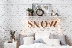 Ett rymligt vitt ljust sovrum i en vindstil med en dekorerad julgran arkivfoto