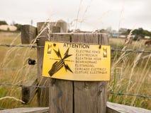 Ett säkerhetstecken på det elektriska staketet för lantgård Arkivfoto
