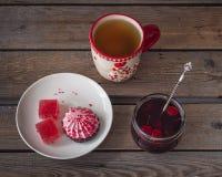 Ett sött mellanmål med tranbärmarshmallower och marmelad, te i ett stort keramiskt rånar och en exponeringsglaskrus med körsbärsr arkivbild
