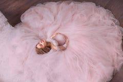 Ett sagolikt magiskt foto av en attraktiv nätt gravid flicka med blont hår i en storartad storartad rosa klänning royaltyfria foton