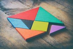Ett saknat stycke i ett fyrkantigt tangrampussel, över trätabellen Arkivbild
