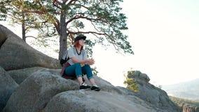 Ett sammanträde för ung kvinna på överkanten av berget som ser det härliga landskapet som tänker om liv En flicka som går på lager videofilmer