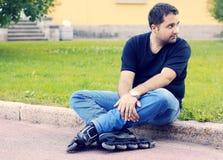 Ett sammanträde för ung man åker rullskridskor in Royaltyfri Fotografi