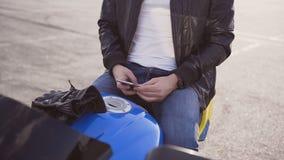 Ett sammanträde för ung man på hans motorcykel och handstil SMS på hans telefon lager videofilmer