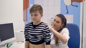 Ett scgoolboy väntar på en stetoskopexamen för att vara över arkivfilmer