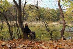 Ett skäggigt mansammanträde på en trädstubbe i höstskogen Royaltyfria Bilder