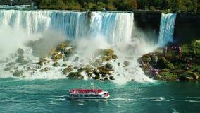 Ett skepp med turister seglar under det berömda Niagaraet Falls Sikt från den kanadensiska kusten arkivbilder