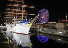 Ett skepp och ett ferrishjul med belysning på den mörka himmelbakgrunden Cityscape av Yokohama Arkivbilder