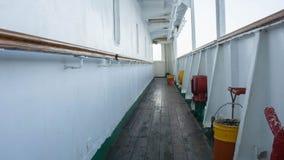 Ett skeppdäck med det red ut gamla träfartyggolvet och räcket på sidovitväggen royaltyfri foto