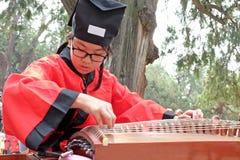"""Ett skolbarn som är iklätt Hanfu för den kinesiska traditionella dräktâ€en """"kläder, spelar det kinesiska traditionella musikinstr Arkivbilder"""