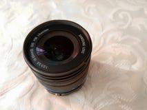 Ett skott av en kameralins med den blåa remsan på ett vitt tyg, Samsung NX serielins royaltyfria bilder