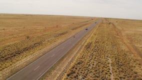 Ett skott av en lång väg och ett brett brunt fält arkivfilmer