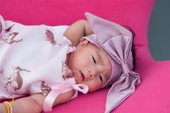Ett skott av ett gulligt behandla som ett barn flickan med den purpurfärgade huvudbindeln, medan att sova och att spela på den ro Royaltyfria Foton