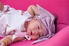 Ett skott av ett gulligt behandla som ett barn flickan med den purpurfärgade huvudbindeln, medan att sova och att spela på den ro Royaltyfria Bilder