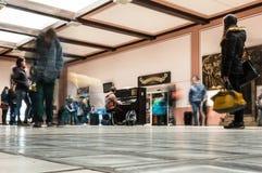 Ett skott av folk som är rörande runt om en pianist som spelar på en flygplats Arkivbild